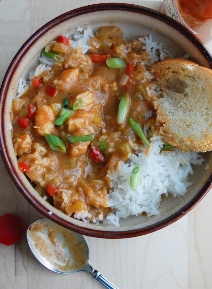 Bowl of shrimp etouffee with rice and a piece of bread with spoon