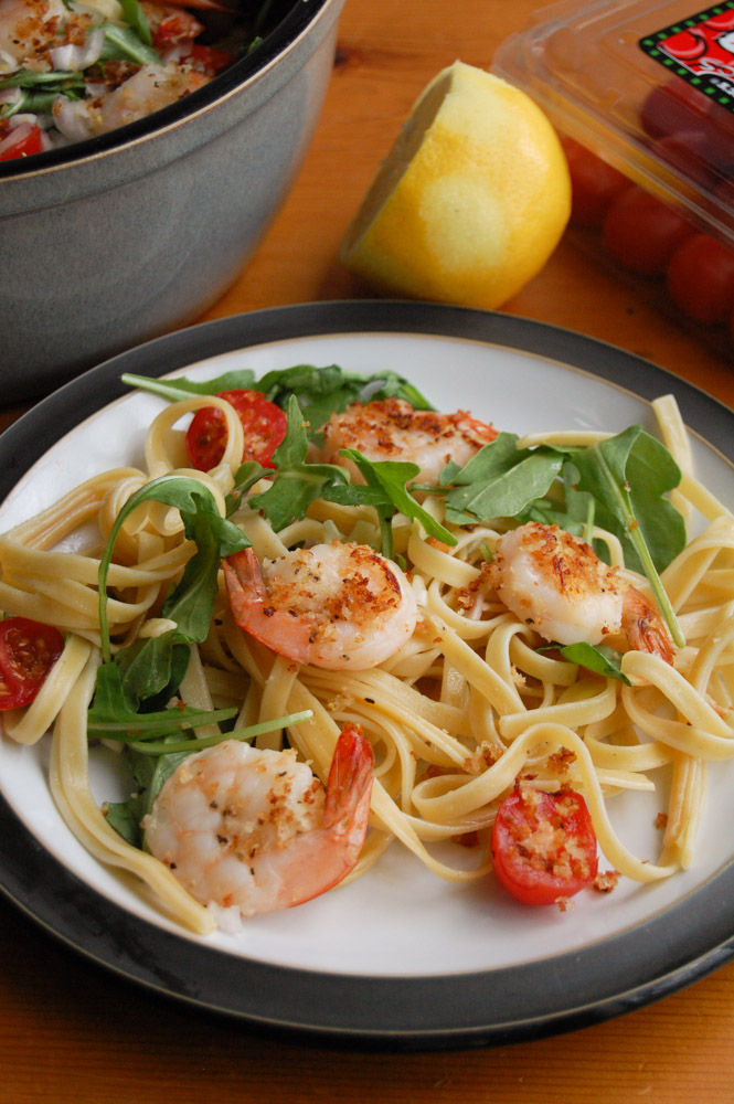 Shrimp and Arugula Pasta on a plate with lemon and tomatoes on a table
