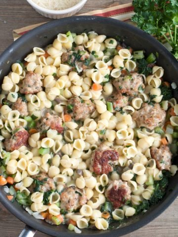 Mini pasta shells with meatballs in a skillet.