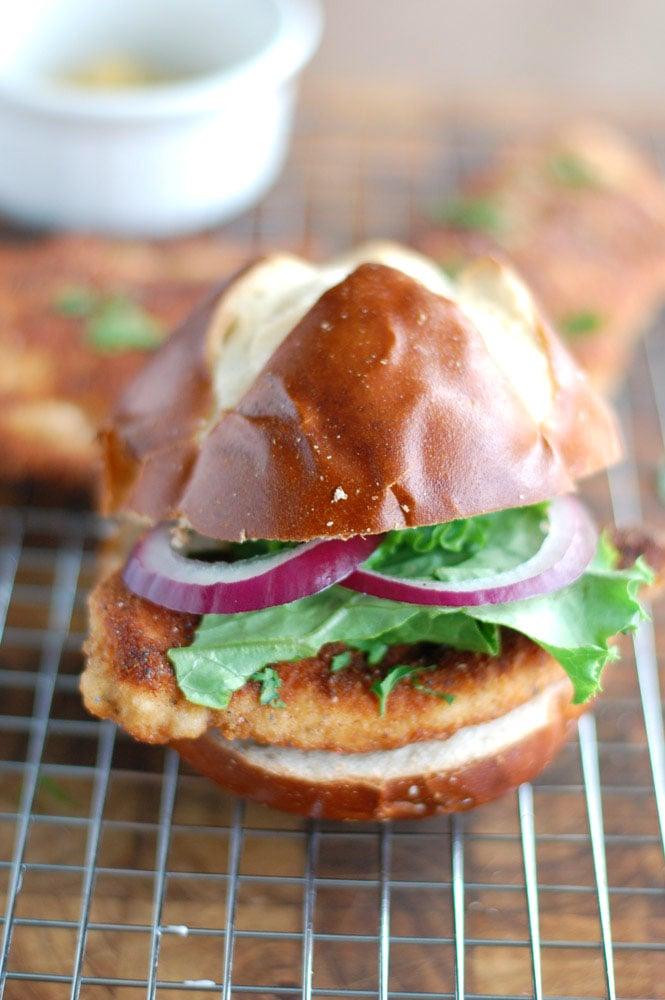 chicken schnitzel sandwich on a pretzel bun on a wire rack