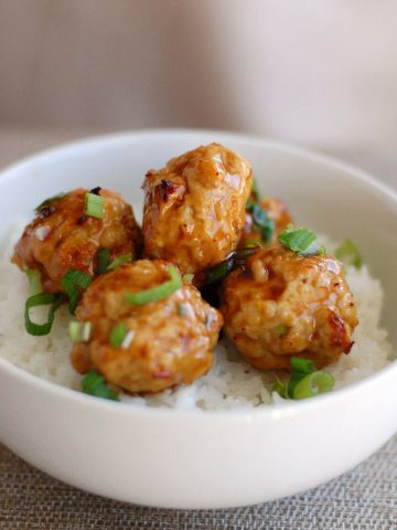 Chicken meatballs on rice in bowl.