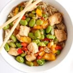 Chicken and edamame in bowl with chopsticks.
