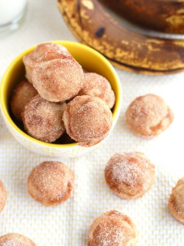 Donut holes in bowl with bananas.