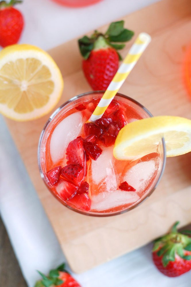 Top view of glass with strawberry lemonade and strawberries and lemon beside the glass.