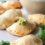 Chicken empanadas on a plate with guacamole.