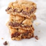 Oatmeal chocolate bar squares stacked on table.