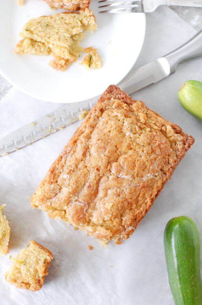 Zucchini Bread Sliced on a table with knife and a plate and fork.