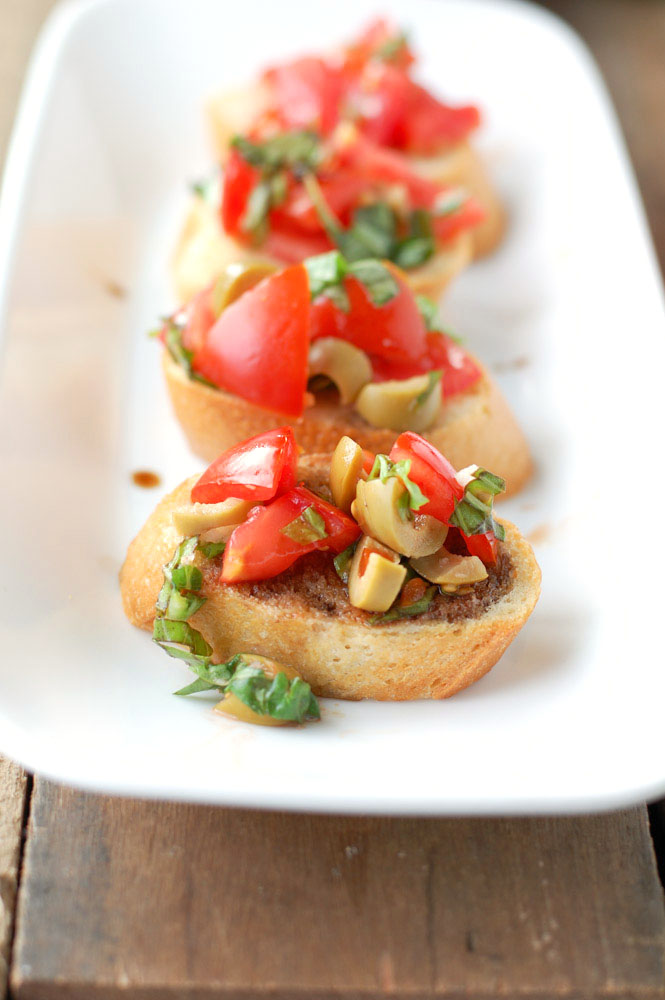 Pieces of bread with green olives and tomatoes.