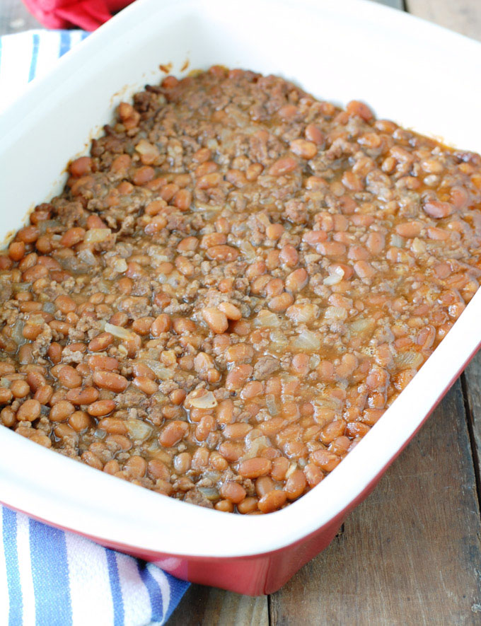 Cowboy baked beans in a red casserole dish