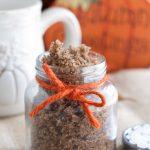 Sugar scrub in a jar with orange ribbon.