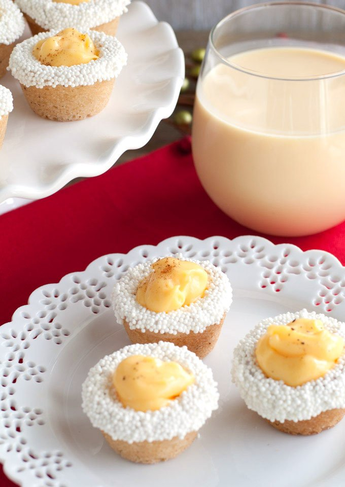 Eggnog cookie cups on a plate with glass of eggnog