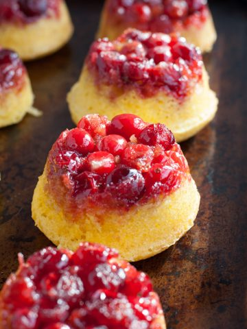 Mini cranberry upside down cakes on a pan.