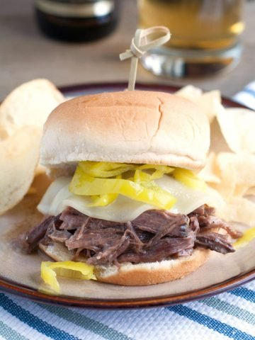 Shredded beef sandwich with cheese and peppers.