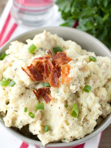 Bowl of mashed potatoes and topped with crumbled bacon.