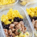 Container with chicken, black beans, yellow rice and pineapple.