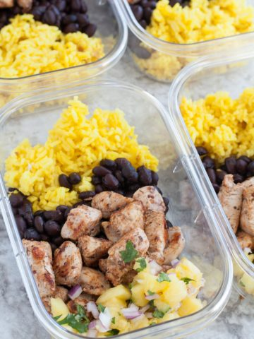 Container with chicken, yellow rice, black beans and pineapple bits.