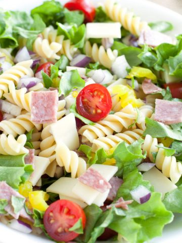 Bowl with lettuce, pasta, tomatoes, salami, cheese and