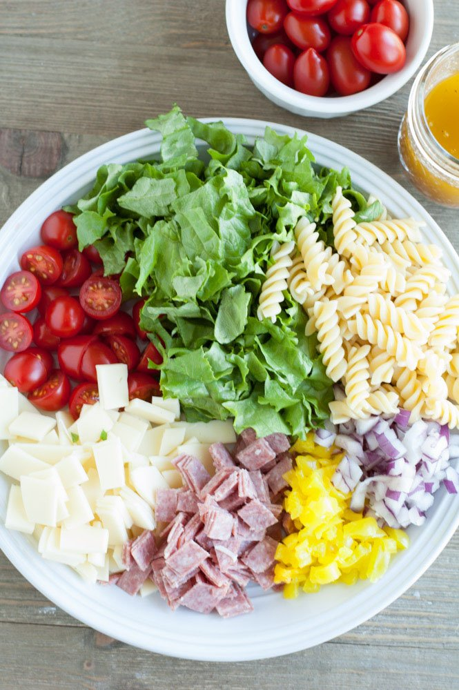 Bowl with lettuce, pasta, tomatoes, cheese, salami, pepper, onion