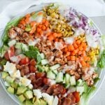 Salad with eggs, bacon, chicken and corn.