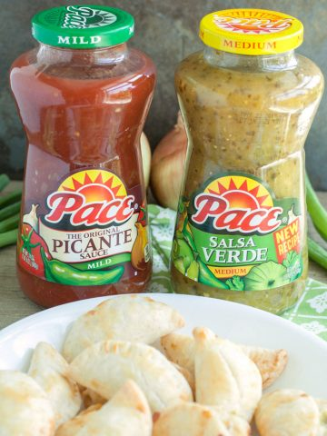 Bottles of salsa on table with bowl of empanadas.