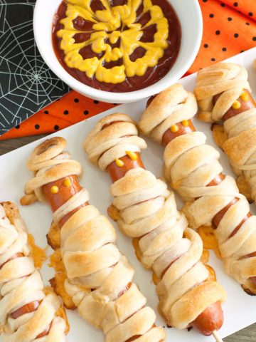Hot dogs wrapped in crescent rolls with bowl of ketchup and mustard.