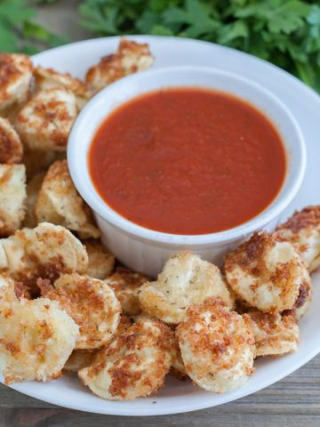 Fried tortellini in bowl with bowl of sauce.