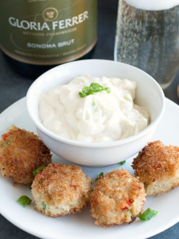Plate with crab cakes and bowl of white sauce.