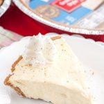 Piece of creamy pie on plate with graham cracker crust.
