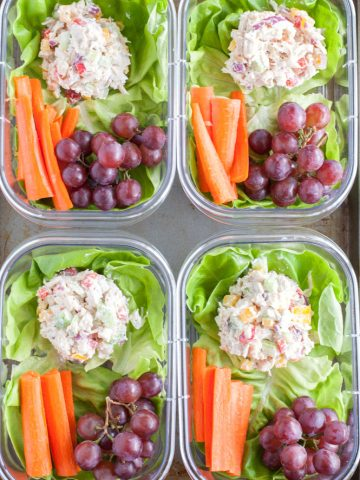 Containers with chicken salad, carrots and grapes.