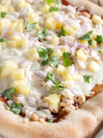 Pizza on baking dish with chicken, cheese and pineapple.