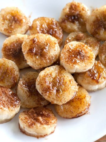 Cooked, sliced bananas with brown sugar on plate.