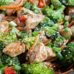 Cooked chicken, broccoli and carrots in a skillet.