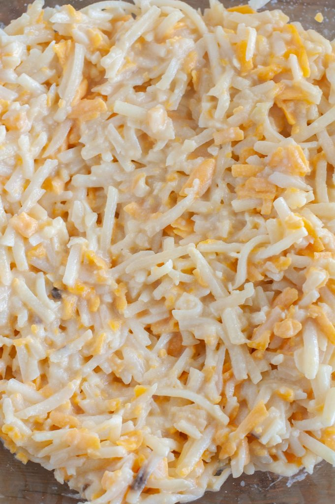 shredded hashbrowns with shredded cheese in a bowl