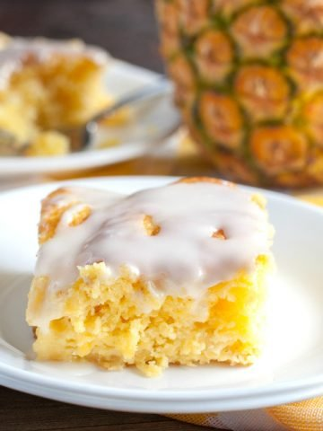 Piece of yellow cake with icing and pineapple in background.