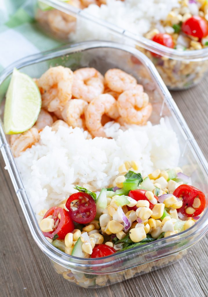 Container with shrimp, white rice and corn and tomatoes.