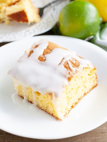 Piece of cake with icing, lemon and limes.
