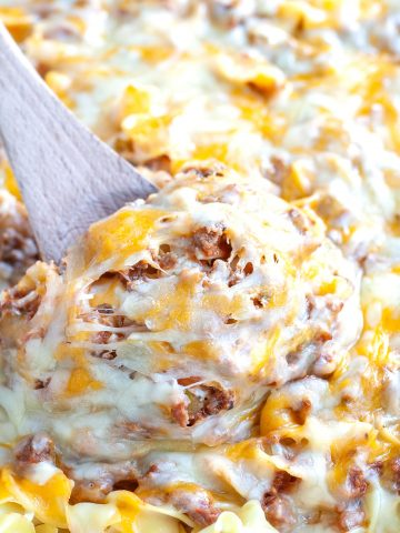 Wooden spoon with pasta, beef and cheese.
