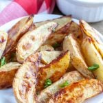 Cooked potato wedges on plate.