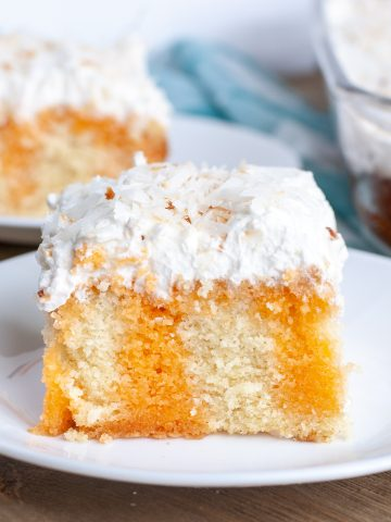 Orange cake on plate with frosting.