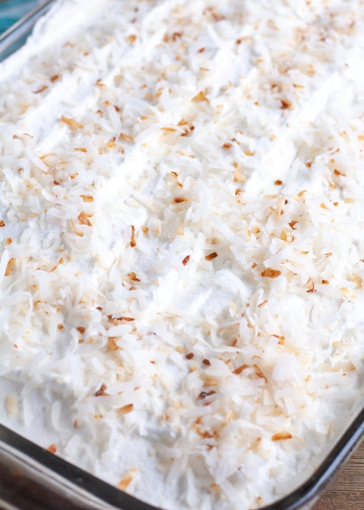 Orange Poke Cake Topped with whipped topping and toasted coconut
