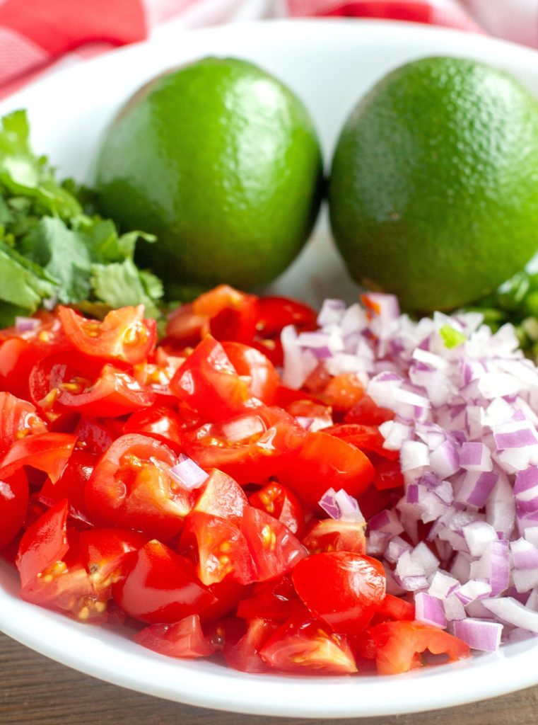 Diced tomatoes, diced red onion, cilantro, 2 limes in a white bowl