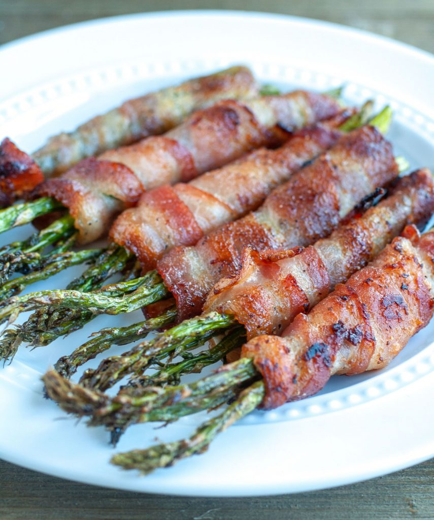 Asparagus wrapped in bacon that was cooked in the Air Fryer on a white plate