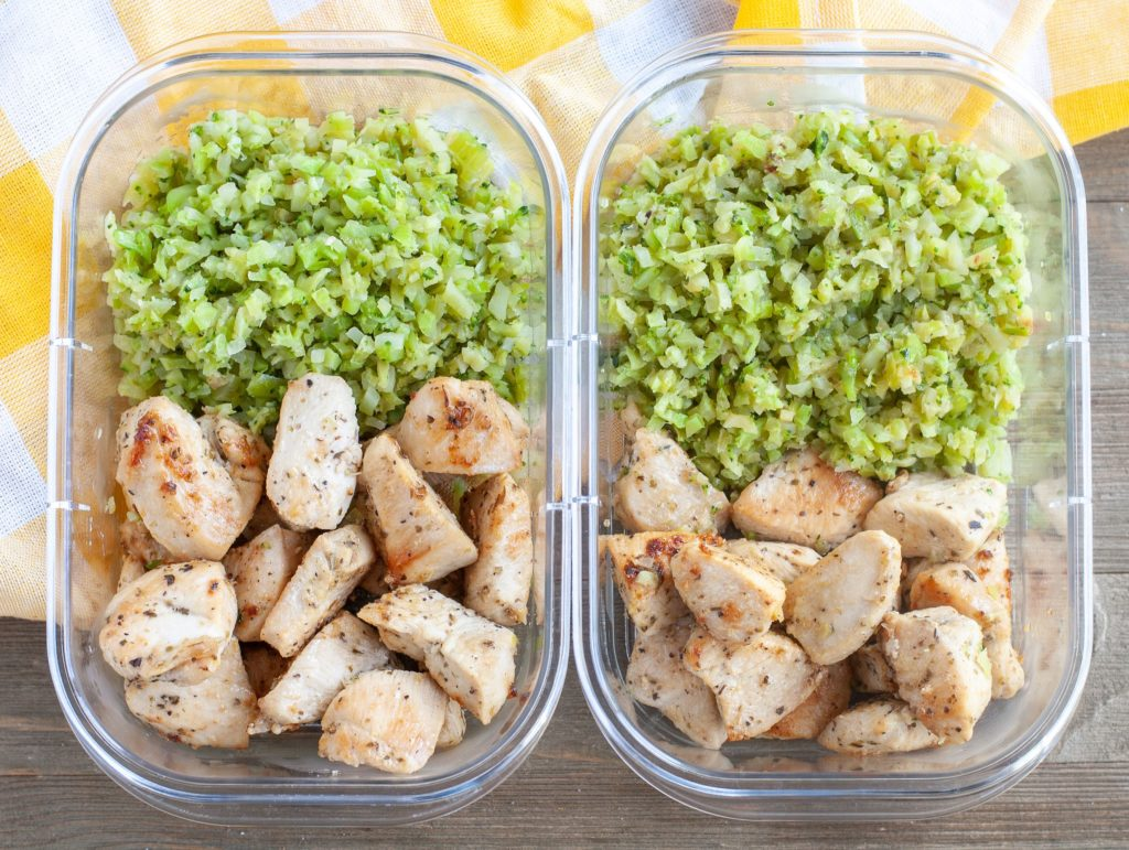 2 meal prep containers with garlic chicken and riced veggies
