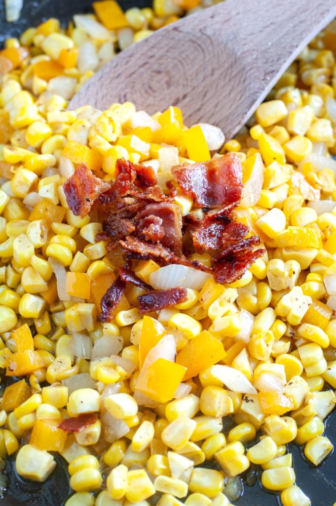 Fried Corn in a skillet topped with crumbled bacon and a wooden spoon.