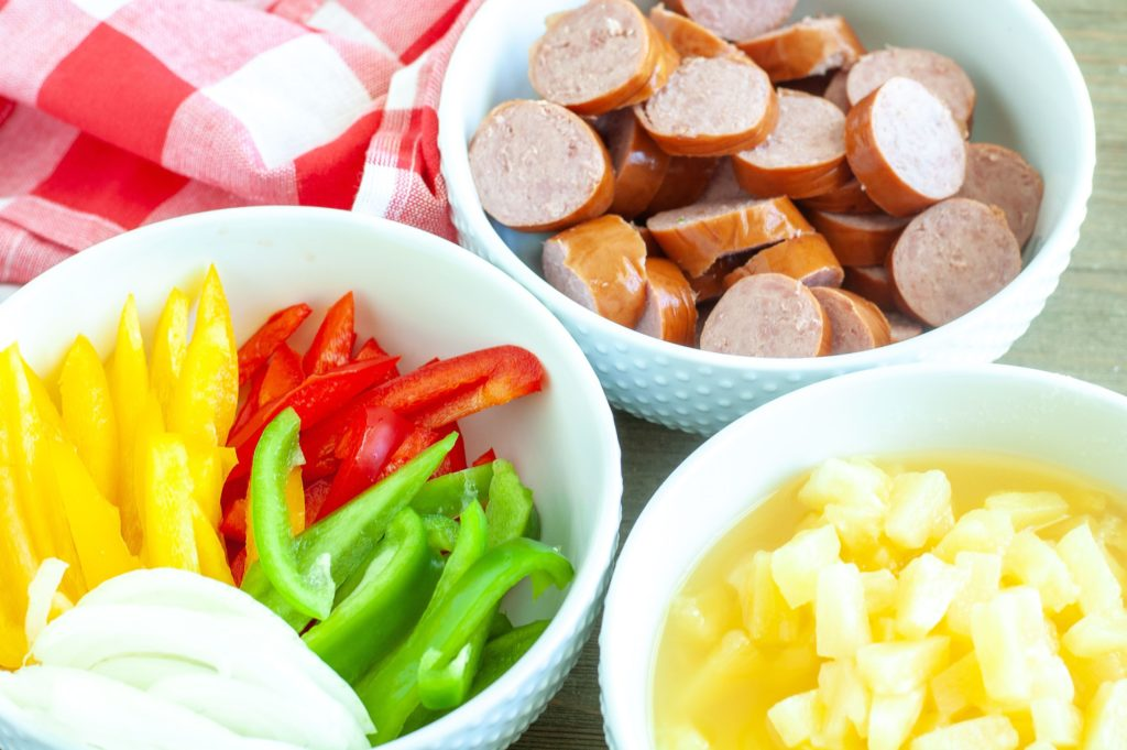 A bowl of bell peppers and onions, bowl of kielbasa and a bowl of pineapple tidbits