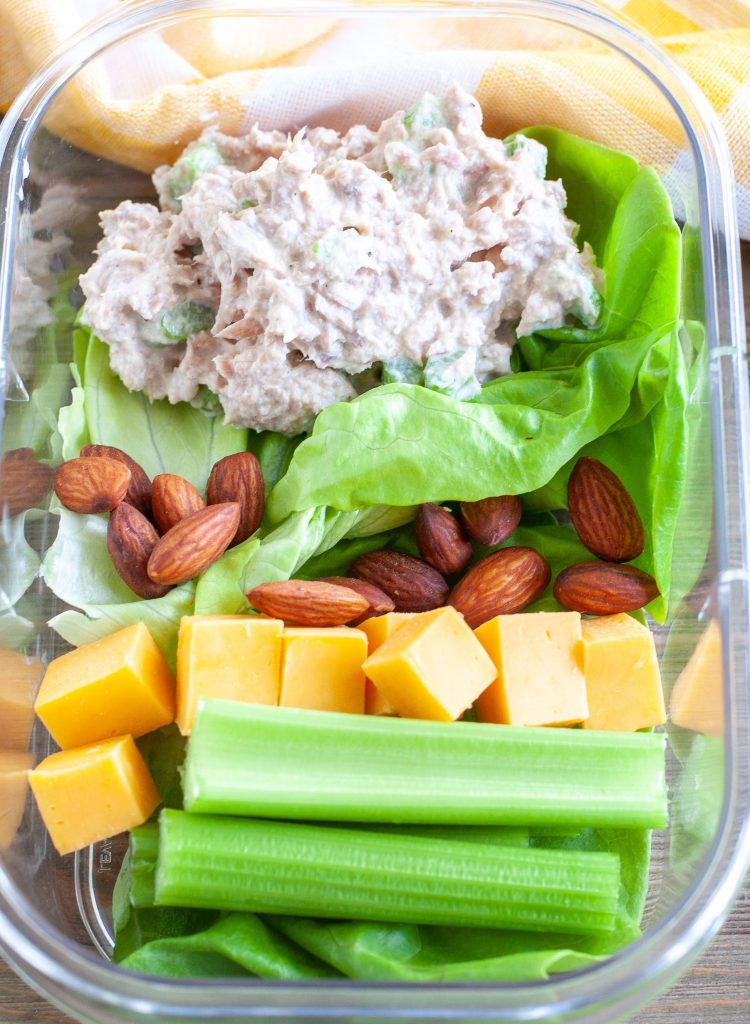Tuna salad, almonds, cubed cheese and celery sticks in a meal prep container.