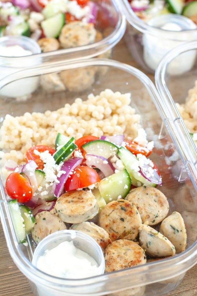 Meal prep container with chicken sausage, couscous and Greek Salad