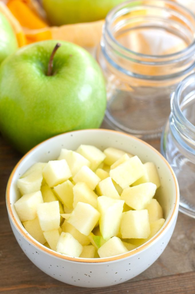 Diced apples in a bowl with empty jars and an apple