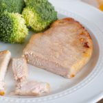 Pork chop on a plate with broccoli.