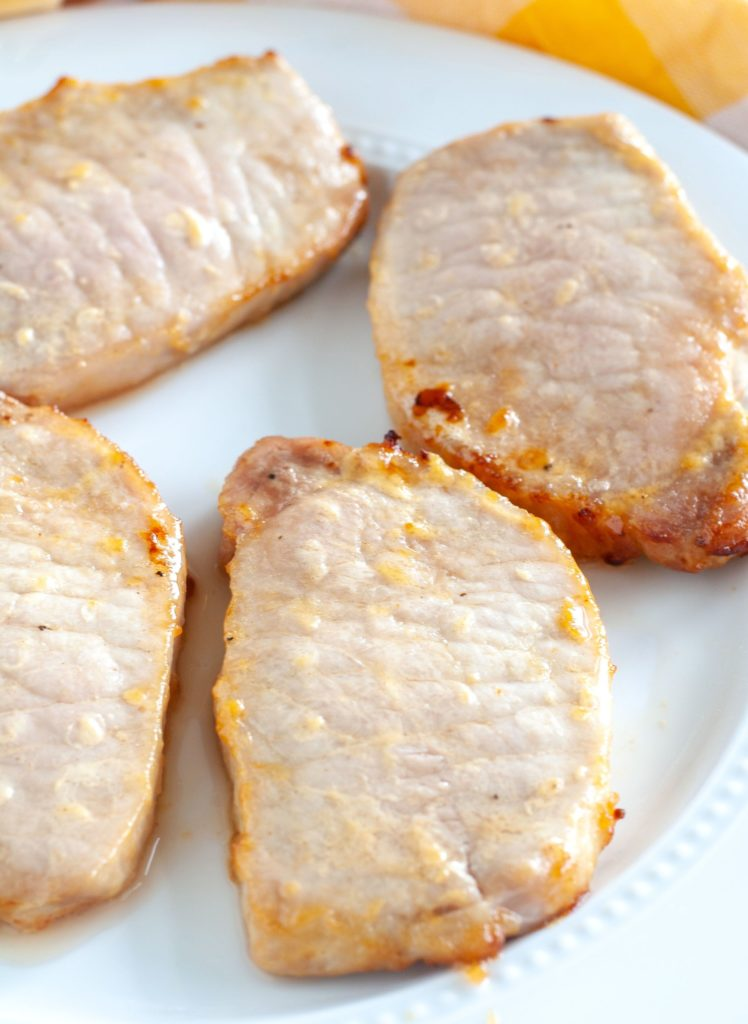4 pork chops on a white plate